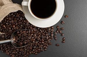 kop kaffe med kaffebønner spredt ud