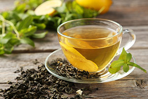 en kop med grøn te omringet af friske grønne te blade