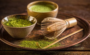 Image of Matcha Tea powder with bamboo whisk and bamboo scoop
